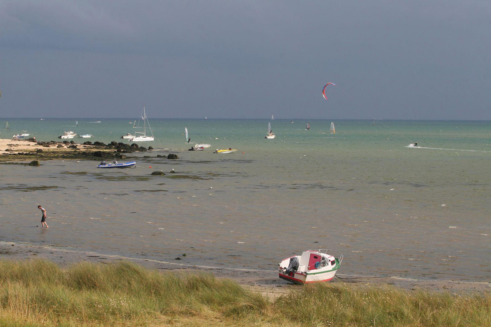 Bateaux, kitesurf et promeneur