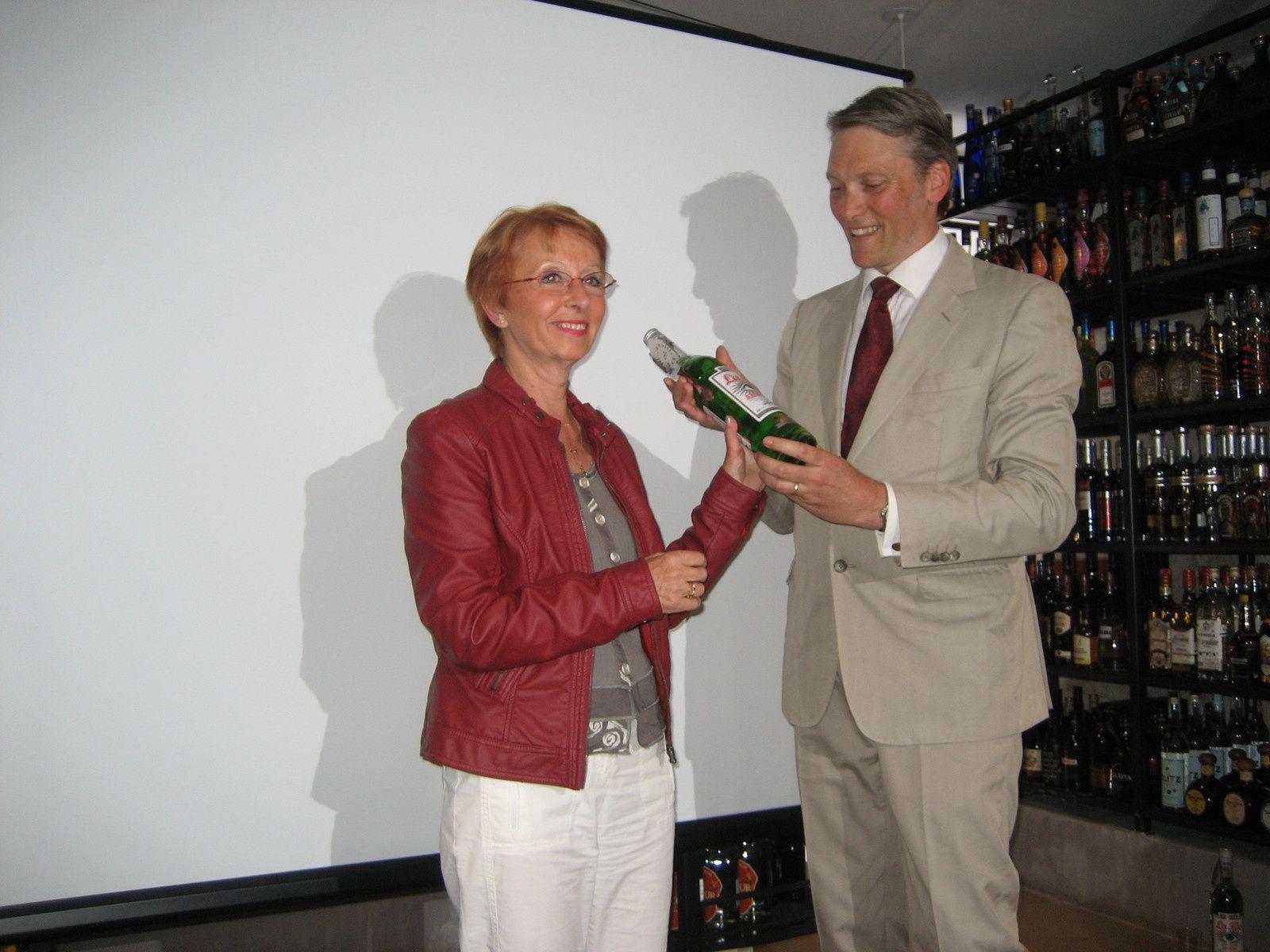Georges Rowley colle sur une une bouteille d'absinthe La Fée la première étiquette libellée ABSINTHE à la Maison du Whisky, Paris, 6ème.