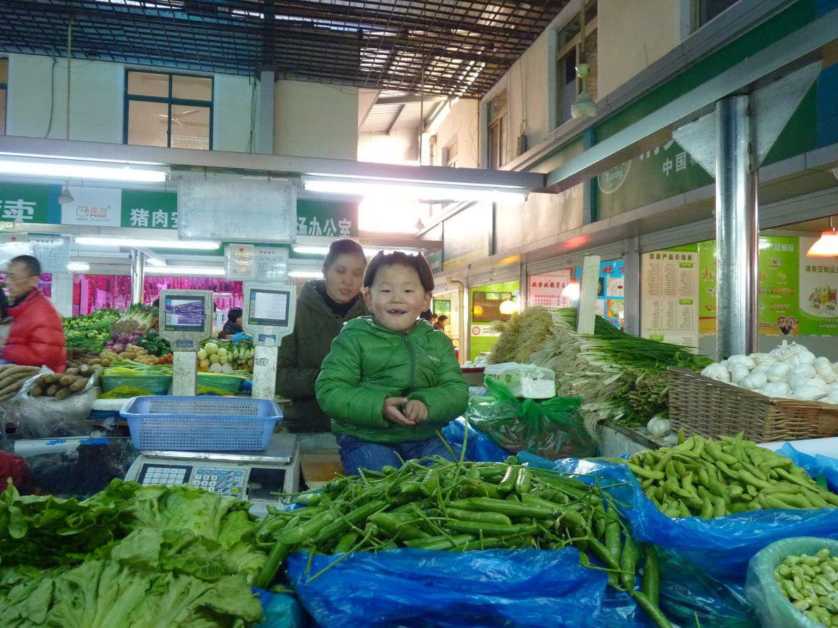 un petit garçon assorti aux légumes vendus par sa maman!!