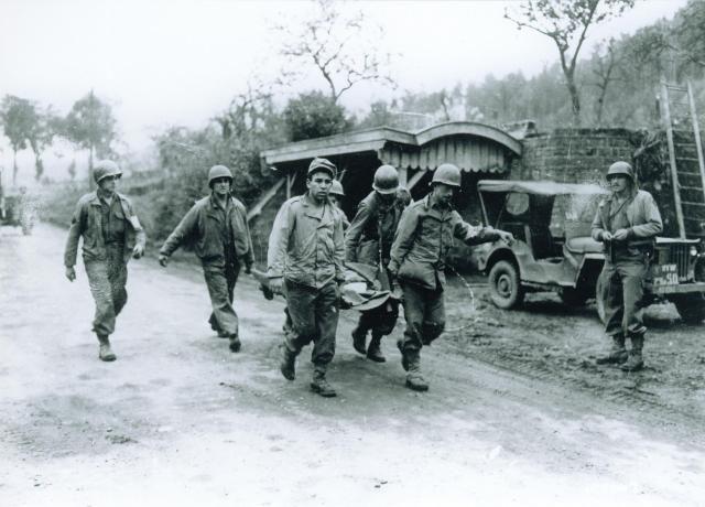 BROUVELIEURES 1944 : Un soldat de la 45ème Division regarde passer un groupe de brancardiers .