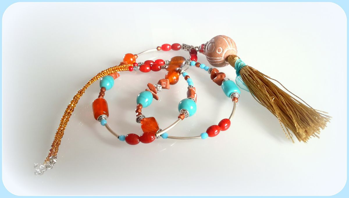 Sautoir monté sur câble , perles céramique et perles de verre . Grosse perle de bois peinte et pompon de fils de soie