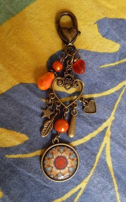 Bijoux de sac bronze et cabochon orangé, accompagné de perles de verre.