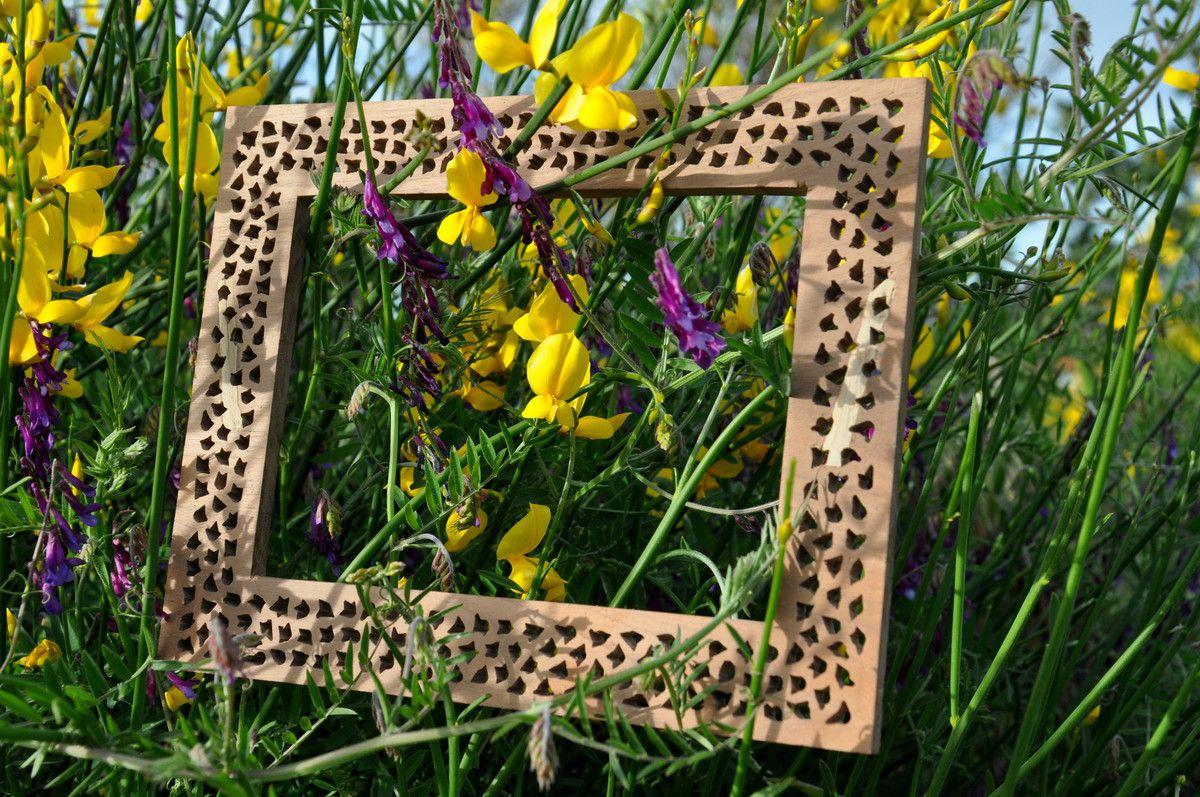 La nature dans un cadre en bois brodé.