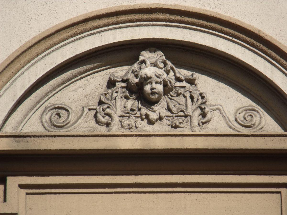 Sous ces fenêtres un petit motif de finition. Pour le premier étage deux motifs différents, un arrondi pour les fenêtres gauche et droite avec une tête d'angelot...