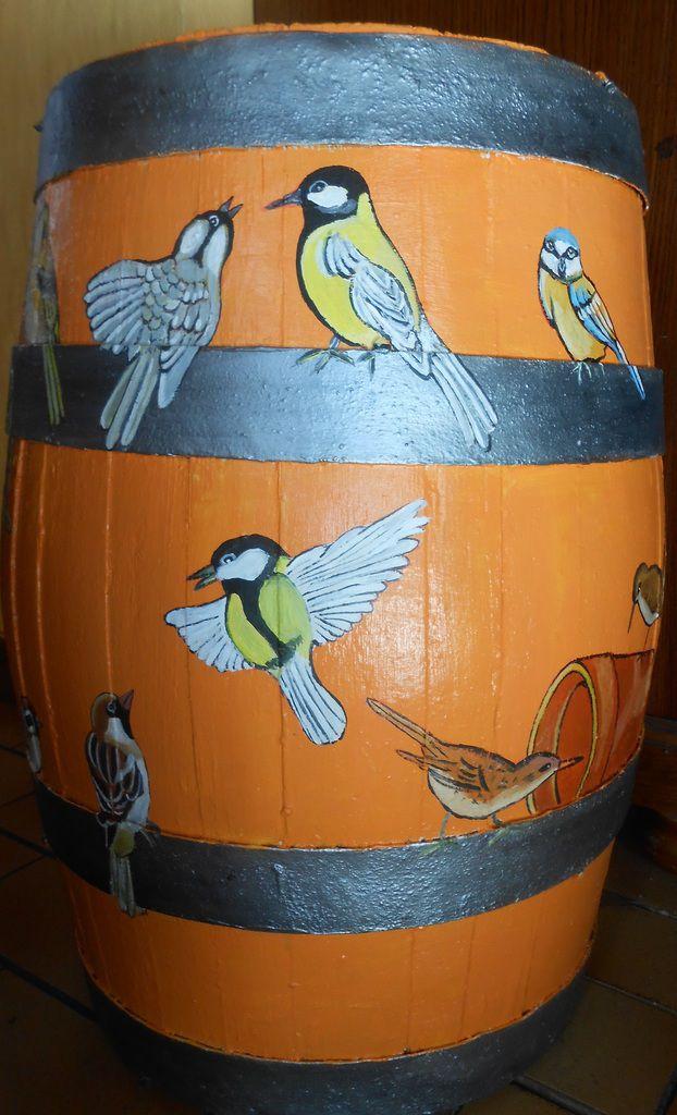 Des oiseaux qui picorent tout autour d'une vieille barrique