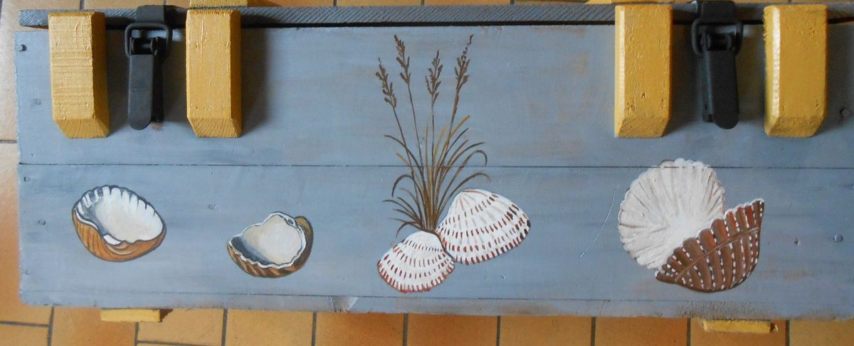 Une malle avec une peinture de voilier, d'étoiles de mer et de coquillages