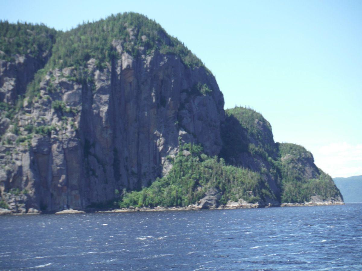 Fjord du Saguenay, falaise, passerelle et voilier dans l'entrée du port de La Baie