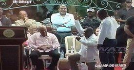 Député mettant un genou en terre devant Martelly.