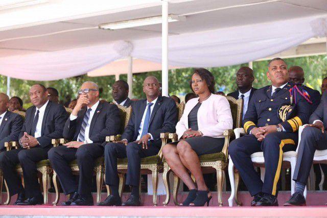 Une photo vaut mille mots : le chef de la Police, Michel Ange Gédéon a droit à une chaise en plastique au moment même où l'on célèbre la police. L'épouse de l'inculpé fait-président - qui n'a pas sa place dans ce type de cérémonie - usurpait  son siège.