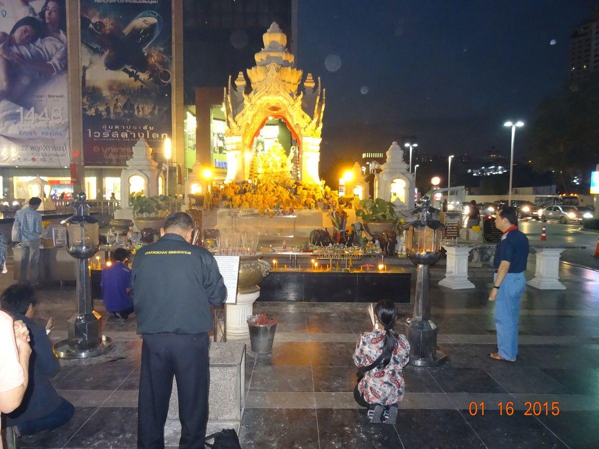 en soirée, devant une représentation de Bouddha, certains prennent le temp de s'incliner pour prier et faire des offrandes