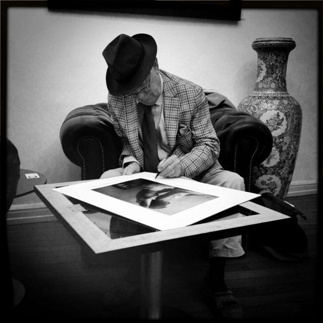 Le photographe David Hamilton, signant une de ses œuvres, en décembre 2012 (Photo: François Besch)
