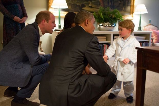 Prince George keeps a close eye on his father, Prince William, while shaking hands with U.S. President Barack Obama at Kensington Palace on Friday. (Pete Souza/The White House via Getty Images)