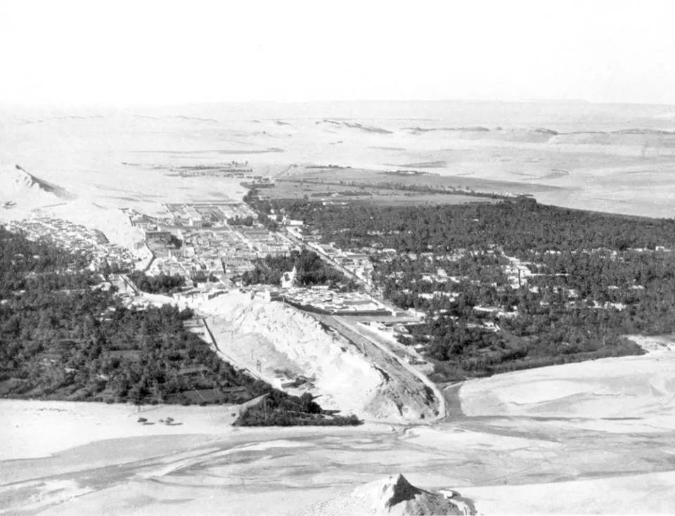 """Laghouat ,les deux palmeraies Sud et Nord séparées par le mont """"Tizgarine"""" ou fut construite la ville sur les flans .(La photo est une prise aerienne très ancienne.)"""