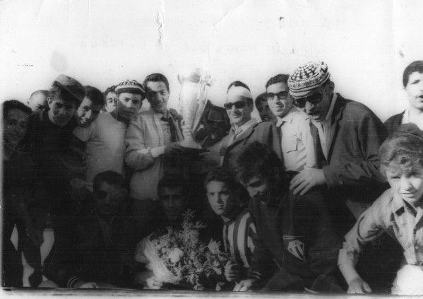L'euphorie de la victoire: joueurs et supporters posent avec la coupe.                                                 Mai 1969 stade municipal de Ouargla.On reconnaît les joueurs Bensalem,Bouzalekh,Moulay entourés de debout:Saci(rahimahouAllah),Regue,Moulay Mostefa,Benahmed Saad,Sedira,le blondinet à l'extrême droite mon ami Abder Benbey.Sans oublier Belli Rouighi.