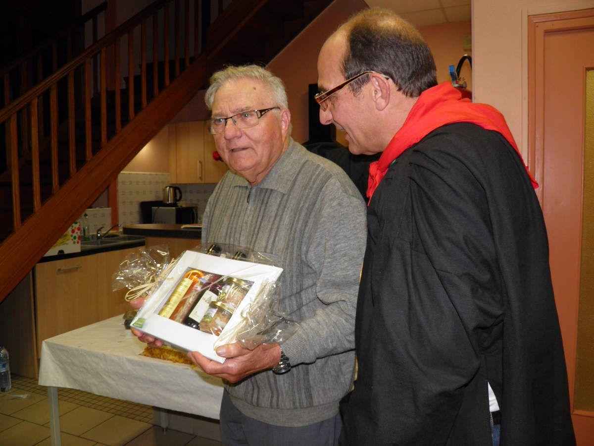 André Hiron reçoit ses cadeaux des mains de Didier, membre à la fois de la Confrérie des Fins Goustiers et des Amis de Sainte-Anne.