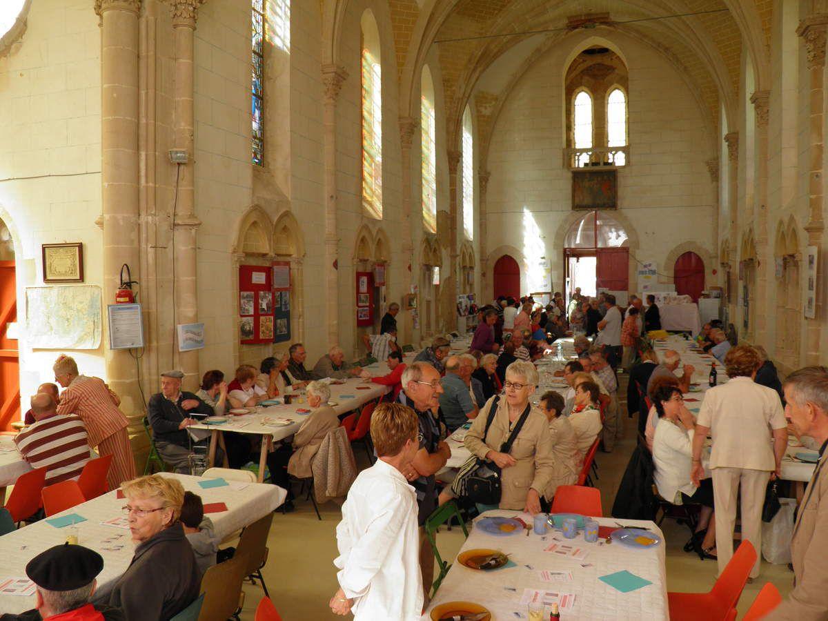 Les participants au repas arrivent et s'installent dans l'église.