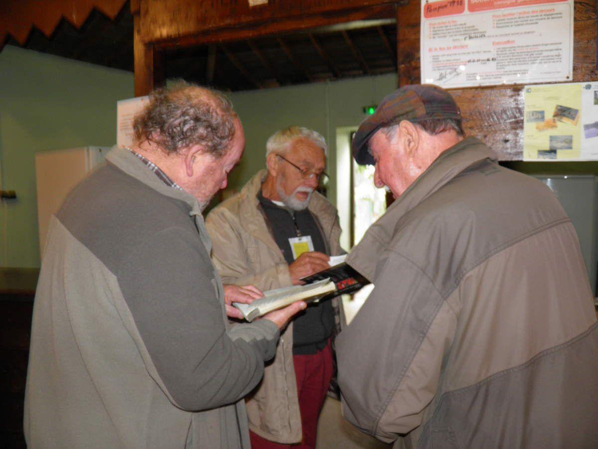 Érick et Olivier se plongent dans leurs livres pour identifier un champignon.