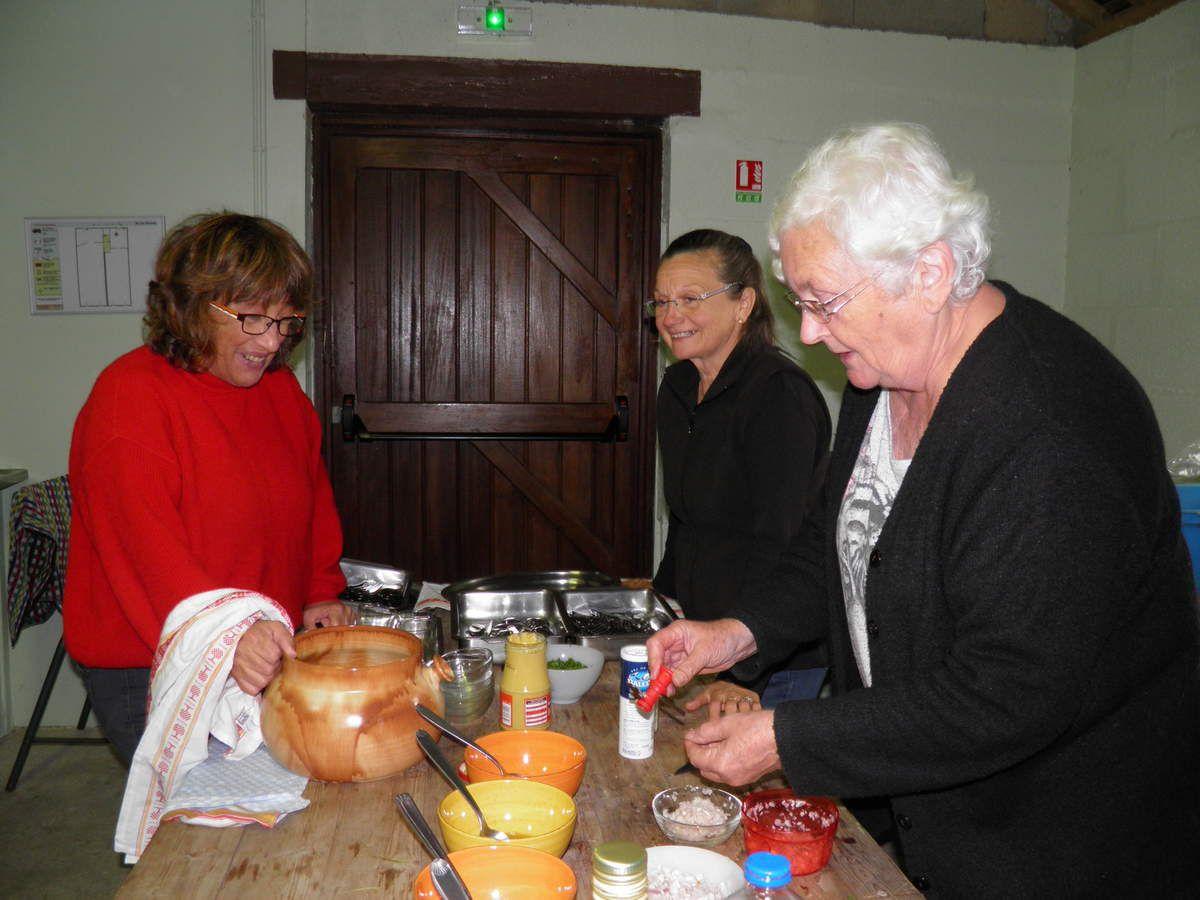 Christiane, de la Confrérie, aide Catherine et Annick, des Amis de Sainte-Anne, à la préparation du repas.
