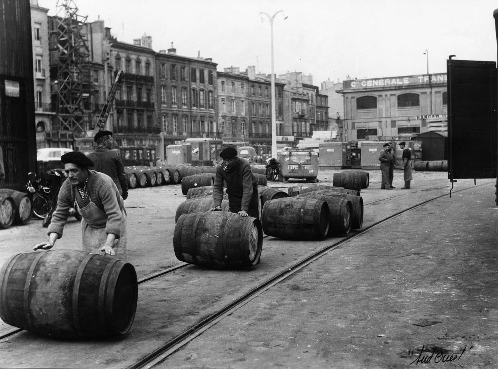 Activité portuaire autour des barriques de vins.