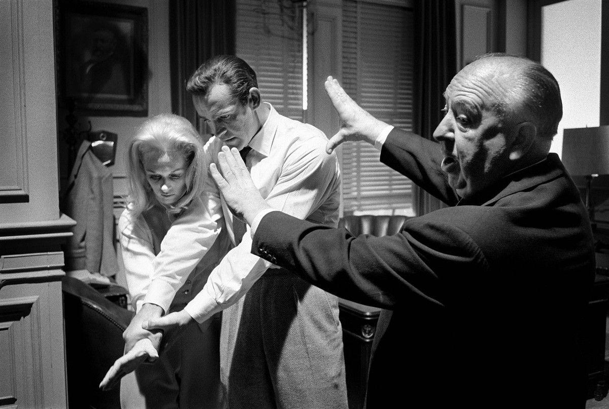"""Alfred Hitchcock montre l'emplacement de la caméra face à Sean Connery et Tippi Hedren sur le tournage de """"Marnie"""", Universal Studios, 1964 © Bob Willoughby"""