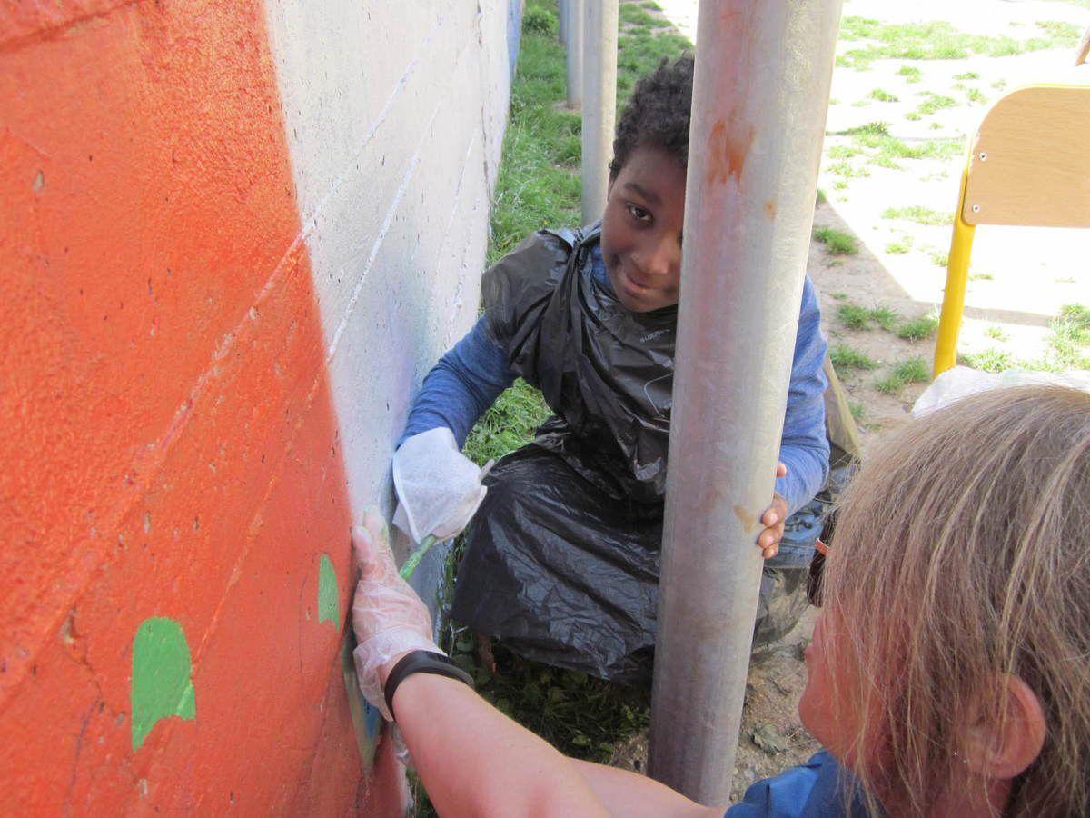 Les CE1 B à la peinture des motifs &quot&#x3B;Cirque&quot&#x3B; sur les murs de la cour de récréation !