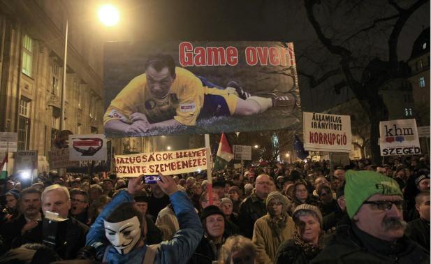 Manifestants tiennent une affiche avec l'image du Premier ministre hongrois Viktor Orban et le texte 'Game Over'