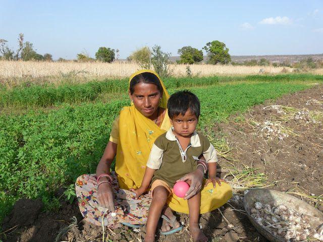 un enfant accompagne sa maman qui travaille dans les champs