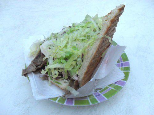 (Un kebab que j'ai pris en photo de profil sans le replier sur lui-même : vous pourrez ainsi remarquer le pain grillé, l'absence de frites et la forme du papier d'emballage qui suit les bords du kebab).