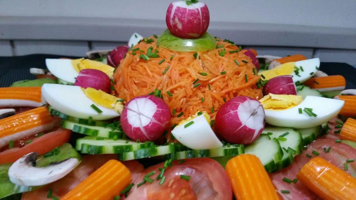 1 - Placer au centre du plateau les carottes râpées légèrement assaisonnées d'un peu de vinaigrette, en formant un dôme. Découper en tranches, lamelles, rondelles ou quartiers les autres ingrédients et les disposer joliment autour des carottes, le tout sur un plateau solide (ici en verre). Alterner des tranches de tomates de couleurs différentes pour varier les saveurs et pour un plus joli effet visuel. Citronner légèrement les champignons pour ne pas qu'ils noircissent. Compléter par les rondelles de concombre cannelées, les quartiers d'oeufs durs et les radis étoilés. Finir en disposant des bâtonnets de surimi et en parsemant sur l'ensemble de la ciboulette ciselée. Réserver au frais en recouvrant de papier absorbant mouillé et égoutté pour préserver l'humidité et la fraîcheur du plat. Servir accompagné des différentes sauces pour que chacun achève l'assaisonnement de son entrée suivant ses envies.