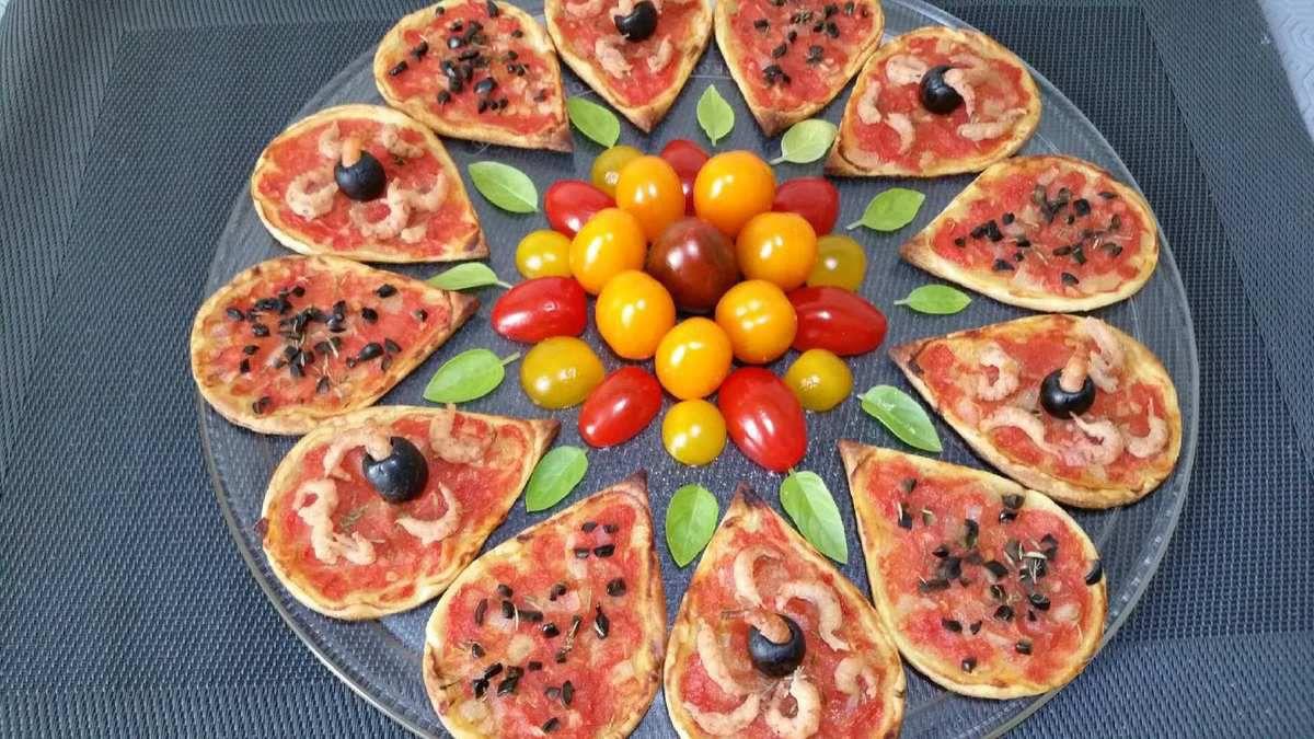 3 - Pendant la cuisson, décorer le centre d'un plateau de service rond (ou d'une grande assiette) d'un assortiment de tomates cerises, répartir ensuite tout autour les pétales feuilletés cuits, et pour finir déposer quelques petites feuilles de basilic. Servir aussitôt. Vous pourrez proposer des sauces variées pour y tremper les tomates cerises.