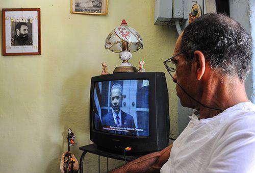 Un ciudadano cubano mira a Barack Obama dando un discurso sobre el restablecimiento de relaciones diplomáticas con Cuba. El presidente visitará Cuba la semana próxima.(AFP/Yamil Lage)