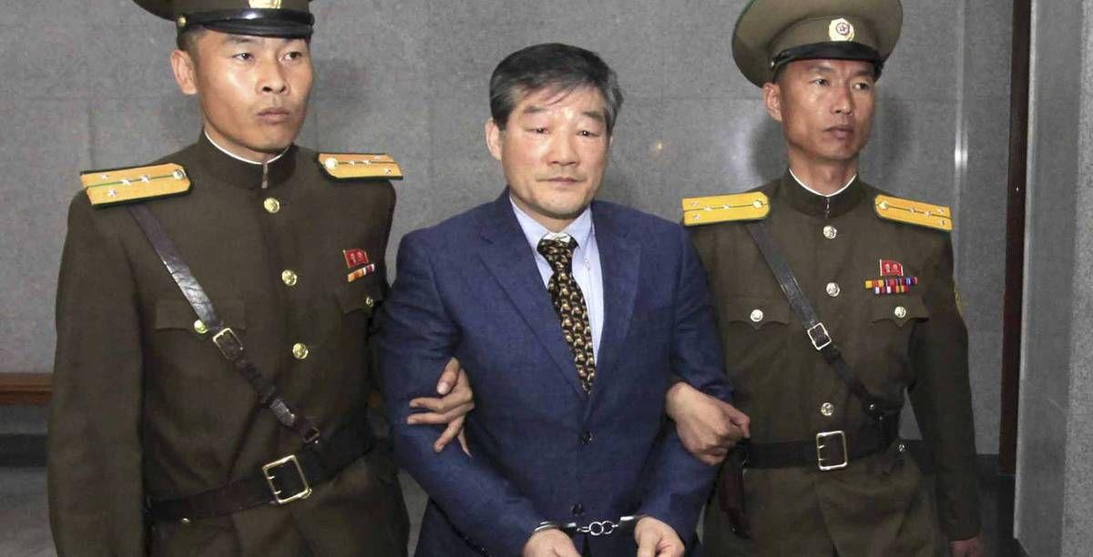 Dos agentes norcoreanos llevan detenido a Kim Dong Chul, este 29 de abril.  AP