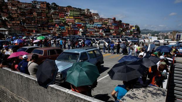 Varios venezolanos hacen cola para entrar en un supermercado de Caracas - ABC