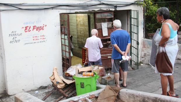 Cubanos hacen cola ante una bodega para adquirir los productos de la cartilla de racionamiento - M. Trillo