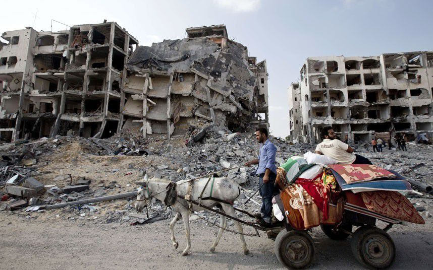 Gaza Under Attack : Palestinian men ride a donkey cart past destroyed buildings in the northern Gaza Strip