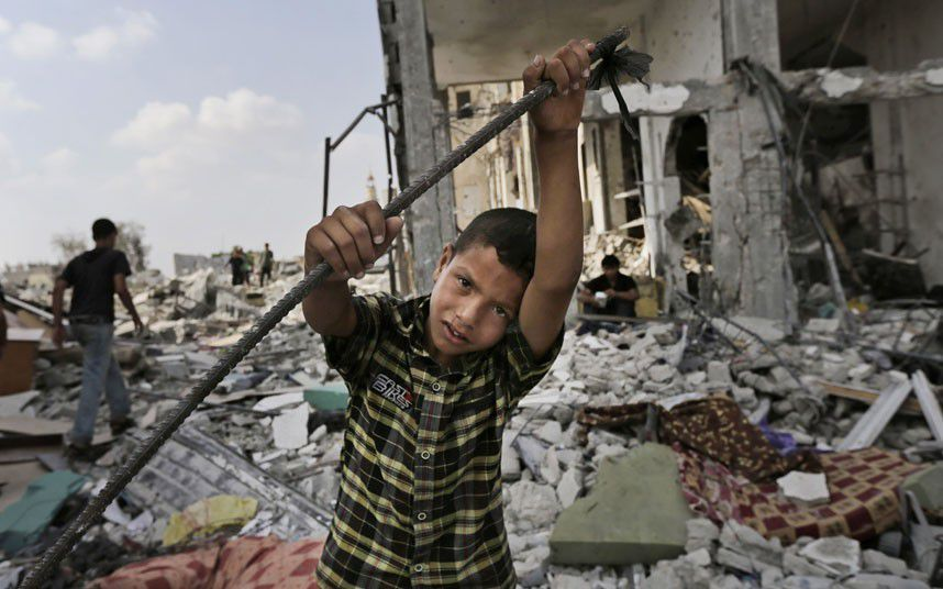 Palestinians inspect damages of the Nada Towers at a residential neighborhood in Beit Lahiya