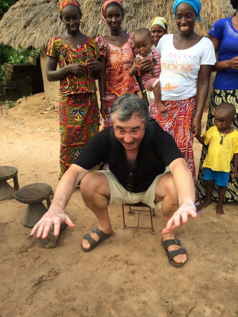 Michel essaie un petit siège d'enfants dans un village.