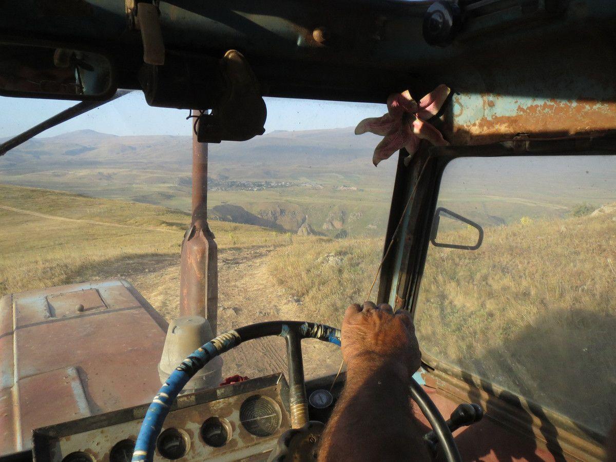 Nous parcourons 5km en tracteur pour atteindre le champ à 2300m d'altitude. La nous pressons 355 bottes de foin de 30kg en 5 heures. Louis monte à bord du vieux tracteur russe biplace et Nat s'assoie à l'arrière avec toute la famille. Nous payons notre dette à la fourche!