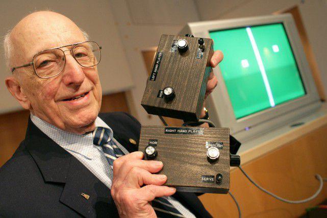 Ralph Baer avec en main les manettes de la console Odyssée. Derrière, sur l'écran, le jeu Tennis.