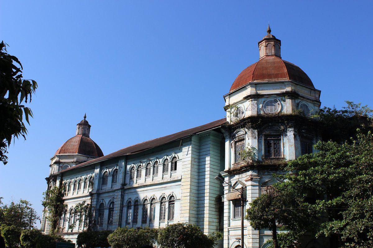 Contraste entre moderne et vieil immeuble colonial décrépi