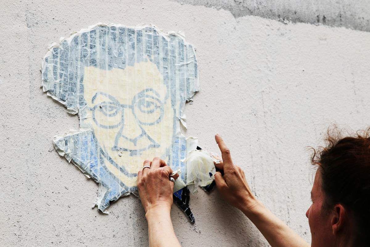 Les street-artistes Dona et K-Bal en trai de poser leur Coluche.