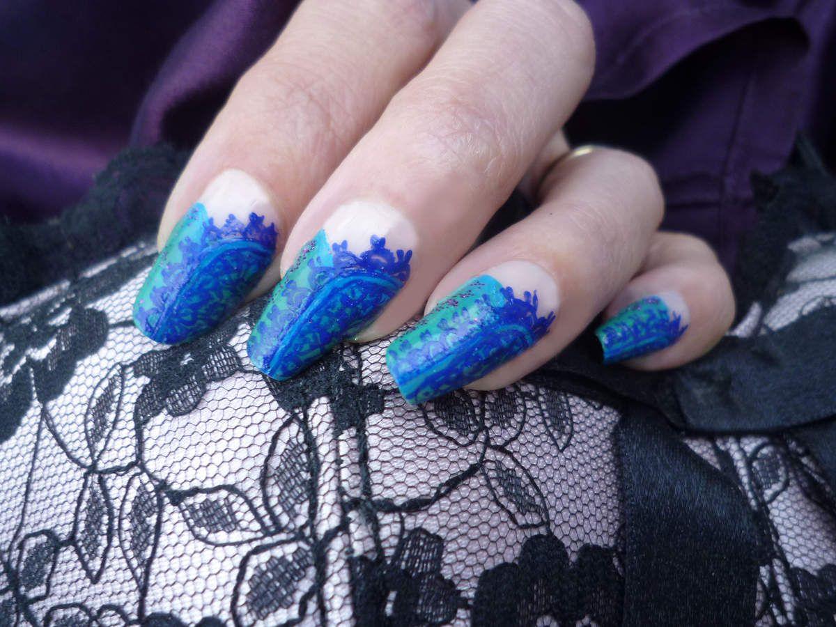 Nail art effet de dentelle bleue sur fond turquoise.