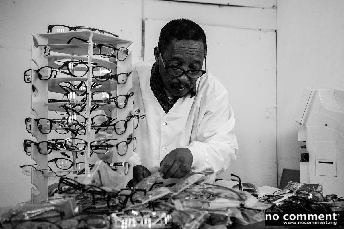 Mr Raymond, lunetier, organise ses lunettes avant l'arrivée des patients.