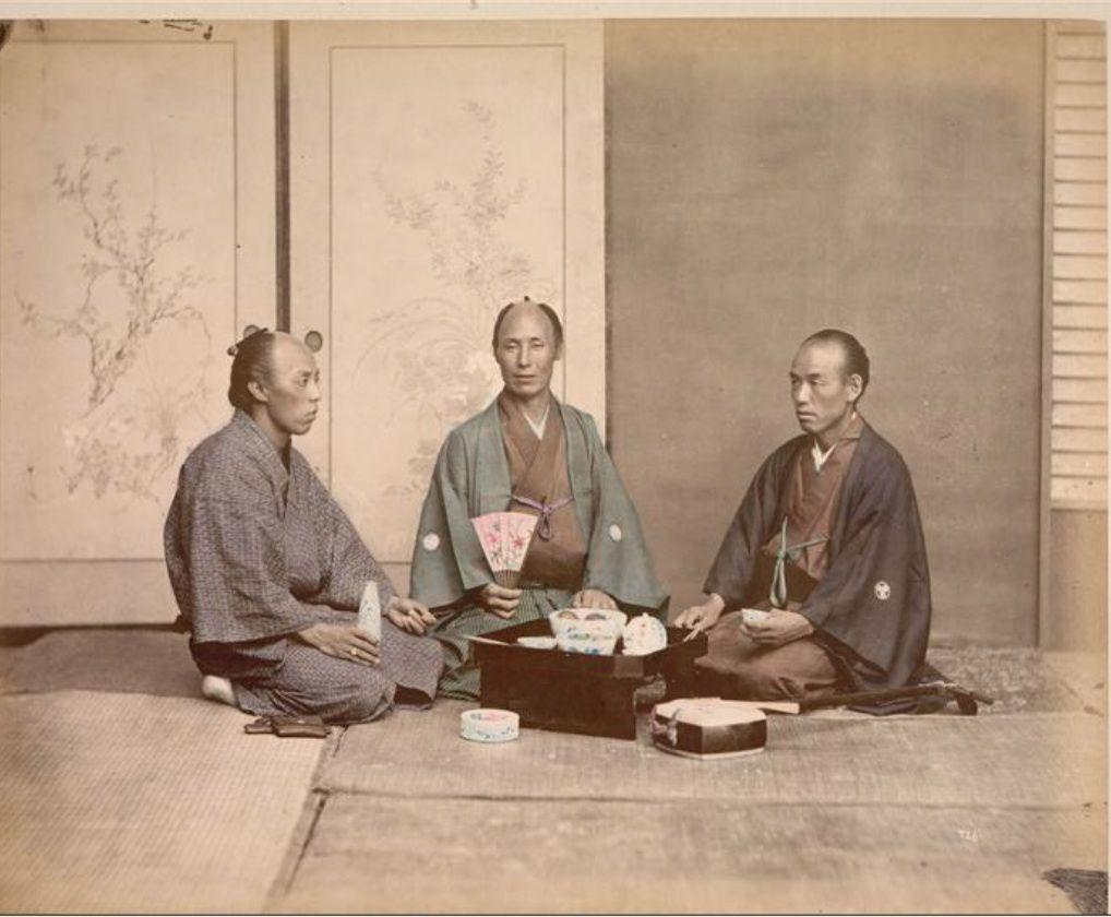 Trois hommes assis dont un tenant un éventail