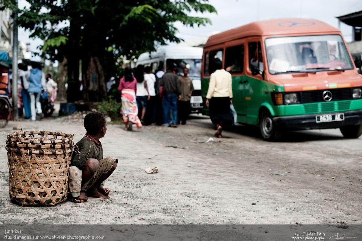 Photo : Un jeune vendeur d'oranges regardant les gens monter dans le bus.