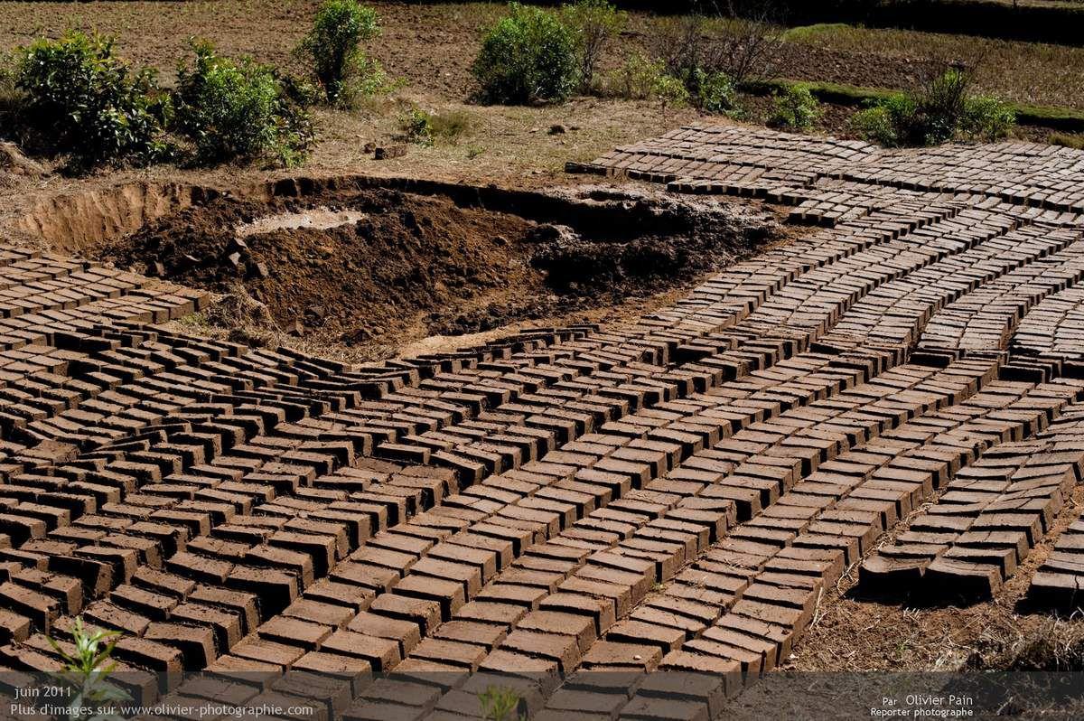 Photo : Une carrière de briques. Elles sont formées puis déposées à même le sol pour sécher au soleil.