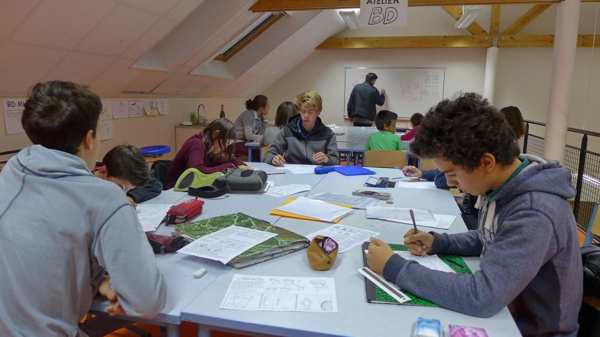 Au premier plan, les membres plus expérimentés de l'atelier jeunes œuvrent sur des petites histoires et exercices mettant en valeur leur créativité.