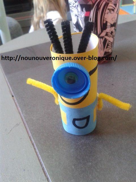 """couper la feuille jaune au dimension du rouleau papier toilette, couper la feuille bleue de la même largeur que la feuille jaune et de la moitié de sa hauteur et pour former le haut de la salopette. Coller l'œil dans le bouchon, puis coller le bouchon sur le milieu de la feuille jaune. Coller la """"salopette"""" bleue sur la feuille jaune. Faire un trait noir de chaque côté du bouchon. (il fera l'élastique qui tient la lunette du minion) . Lui dessiner un sourire et coller la feuille jaune autour du rouleau papier toilette. Coller des chenilles noires pour faire les cheveux du minion puis des chenilles jaunes pour faire les bras."""