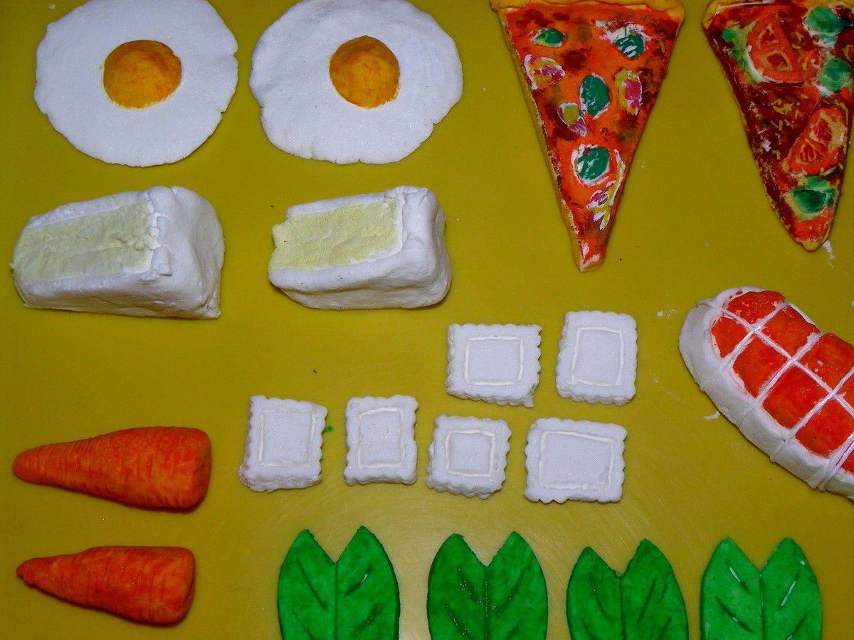Des oeufs au plat, des parts de pizza, des raviolis, du poisson, du steak haché, des parts de camembert, des feuilles de salade, des rondelles de tomate et de concombres, un petit rôti ficelé et des carottes