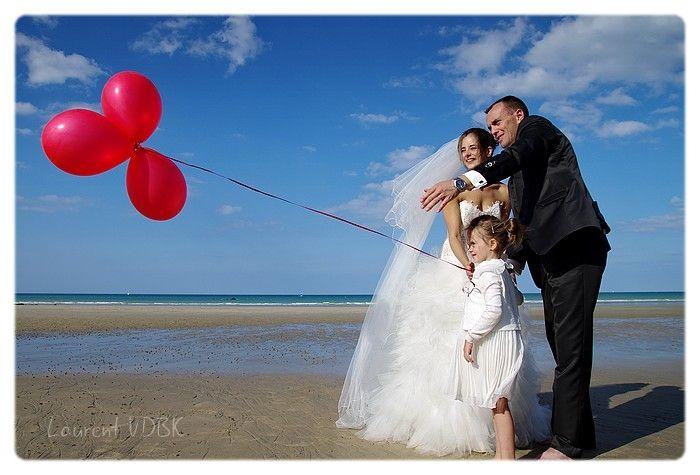 Séance photo Trash the dress sur la plage et jouer avec des ballons rouges qui volent au vent
